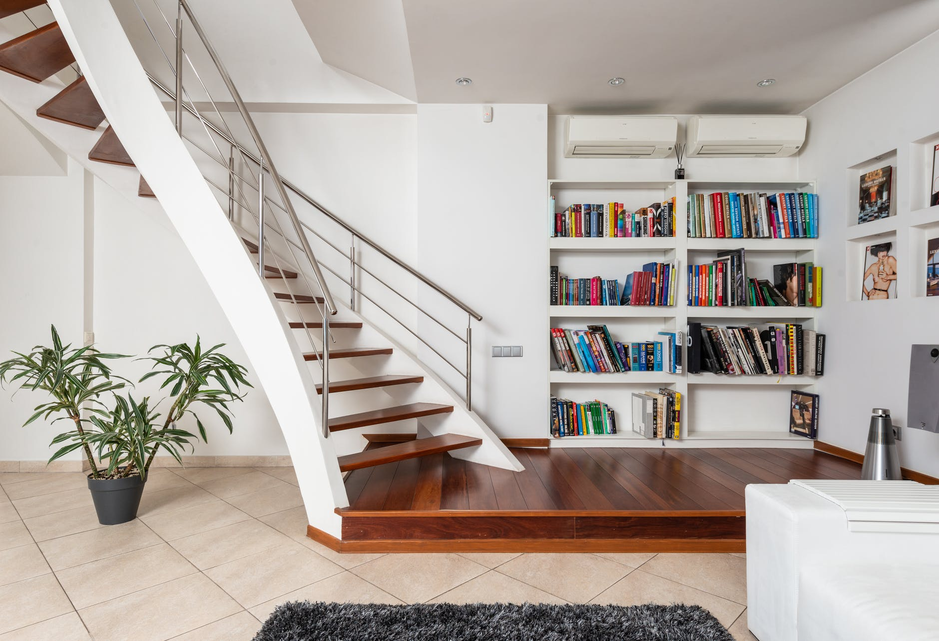 collection of books against modern stairs in house